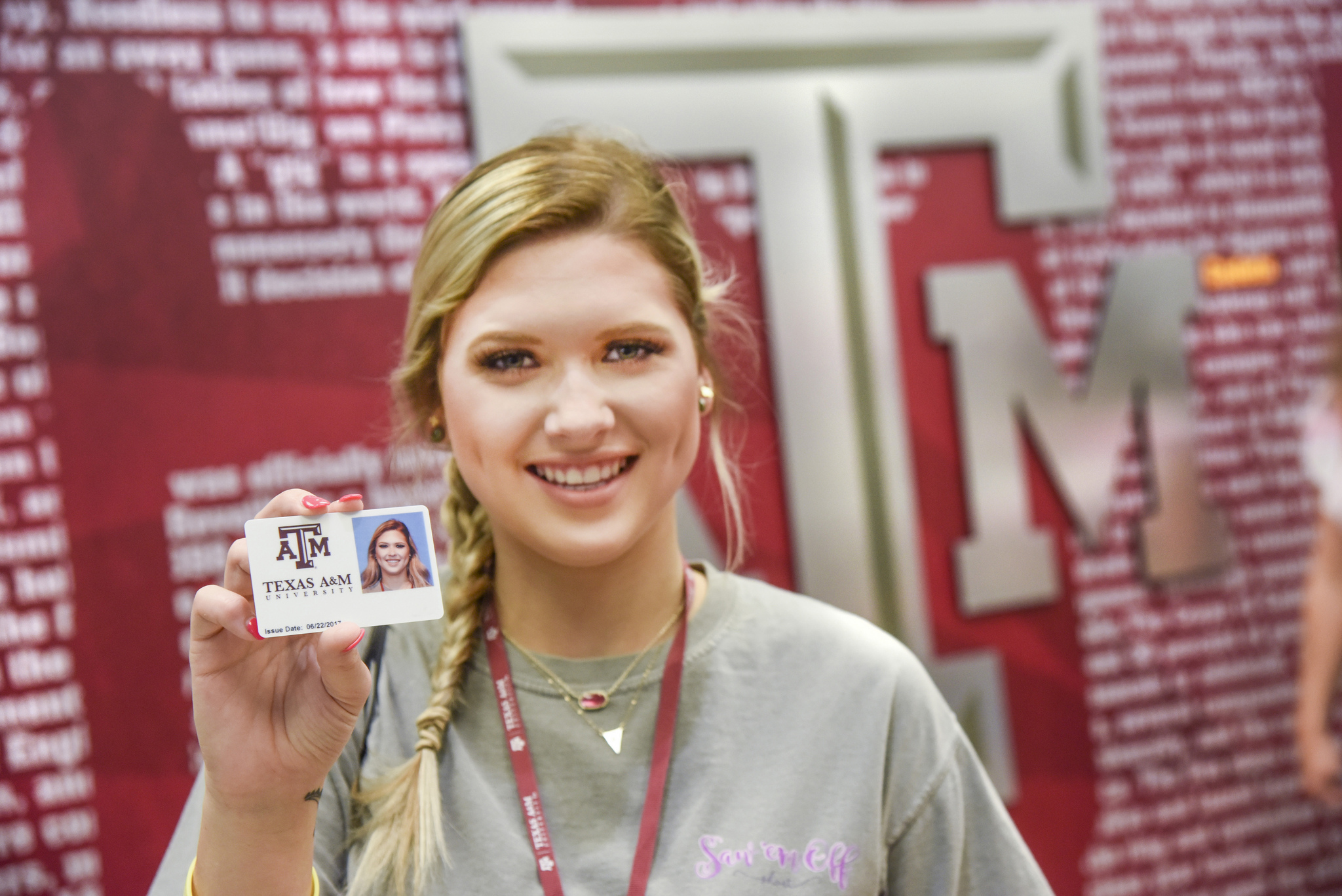 female student holding up an Aggie Card